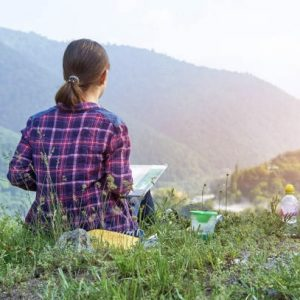 Teenager girl drawing a beautiful mountain landscape at sunset sitting on green grass